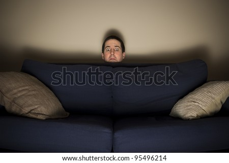 Frightened man peeks over a couch while watching TV - stock photo