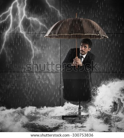 Frightened man protects himself with an umbrella - stock photo