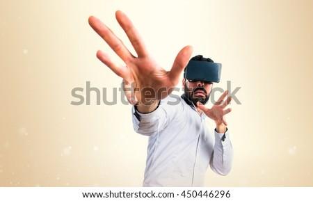 Frightened man using VR glasses over ocher background - stock photo