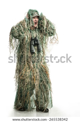 Frightened soldier in camouflage with binoculars - stock photo