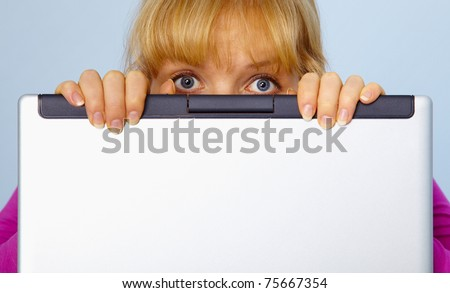 Frightened, the woman was guilty and hides behind a computer screen - stock photo