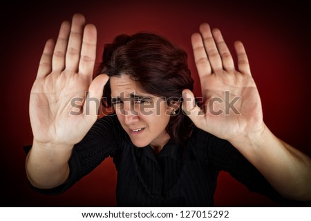 Frightened woman defending herself against an imminent aggression - stock photo