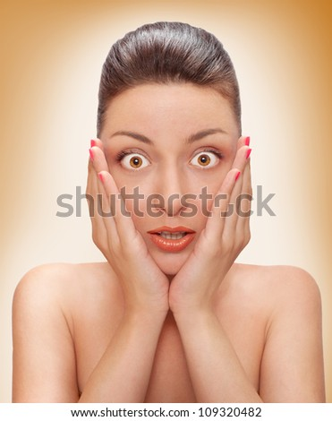 frightened woman with open mouths and eyes with hands near face - stock photo