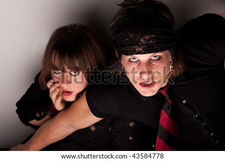 Frightened young couple cowering in a corner - stock photo