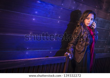 Frightened Young Woman in Dark Walkway Using Cell Phone at Night. - stock photo