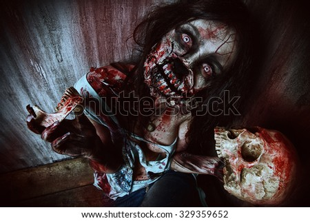 Frightening bloody zombie girl with a skull. Halloween. - stock photo