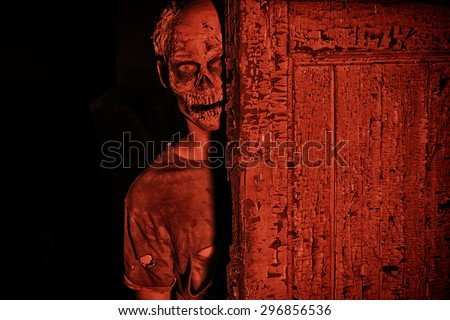 Frightening bloody zombie man in blood-red light. Halloween. - stock photo