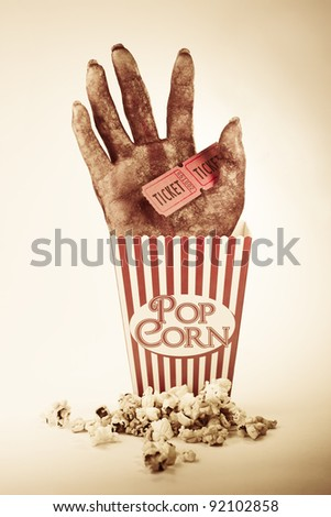Frightening Picture Of A Creepy Sawn Off Hand Poking Out Of A Striped Pop Corn Box Holding Two Cinema Movie Tickets In A Horror Movie Conceptual - stock photo