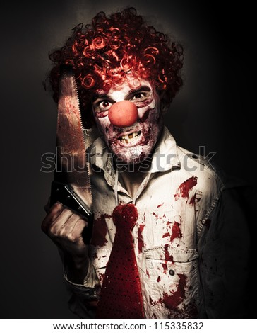 Frightening Portrait Of A Angry Carnival Clown Carrying Amputation Saw In Dark Slaughter House - stock photo