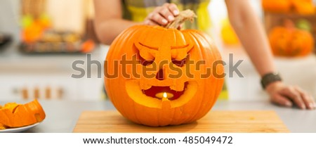 Frightful Treats on the way. Closeup on big pumpkin Jack-O-Lantern in the Halloween decorated kitchen with candle inside