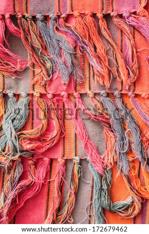 Fringe of a colorful rug as a background - stock photo