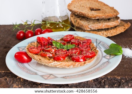 Friselle with tomatoes photographed on a wooden base