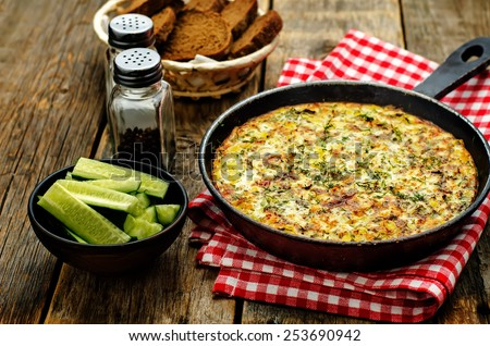 Frittata with chicken and potatoes on a dark wood background. tinting. selective focus - stock photo