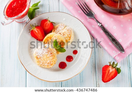 Fritters of cottage cheese with strawberries, sugar powder and mint on wooden background. Selective focus - stock photo