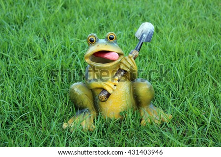 Frog with a shovel on a background of grass - stock photo