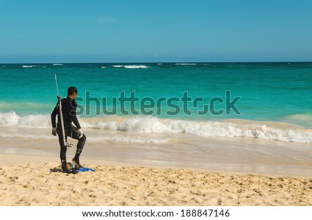 Frogmen on the sandy Caribbean  beach. Snorkeler getting ready to enter the water.