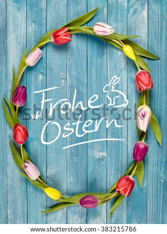 Frohe Ostern, or Happy Easter, greeting card with a colorful fresh multicolored tulip wreath or frame surrounding the central handwritten German text with a cute Easter bunny - stock photo
