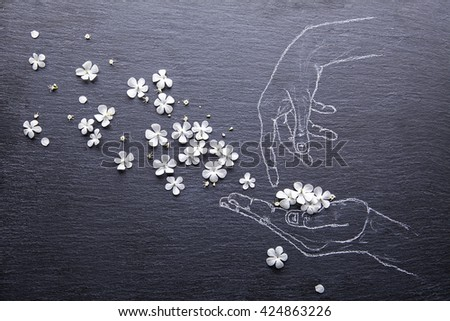 From the hands that painted on a black slate board, fly white flowers - stock photo