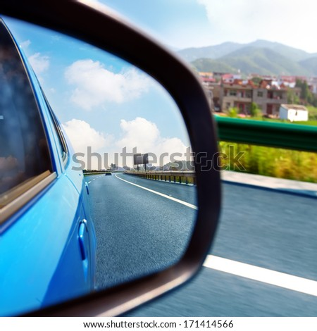 From the inside rearview mirror to see the highway and cars. - stock photo