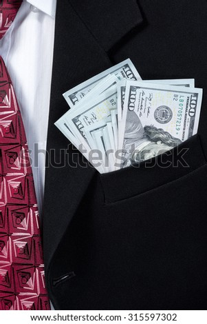 From the outside pocket of his black jacket sticking a pack hundred dollar bills - stock photo