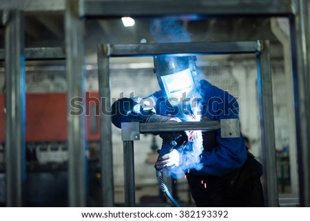 front close-up of a worker wearing a full protective gear, with mask and gloves and a leather apron, welding together two pieces of square pipes into a frame, with several frames already welded  - stock photo