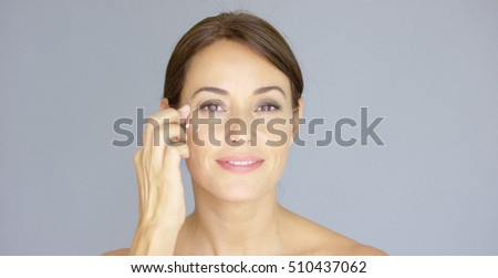 Front close up view on woman touching eyebrow