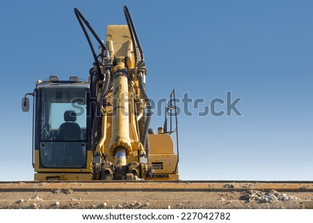 front close view of excavator on blue sky background - stock photo