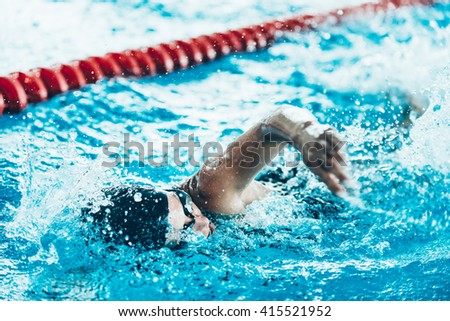 Front crawl swimmer in the pool - stock photo