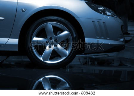 Front detail of new car with reflection, blue toned - stock photo