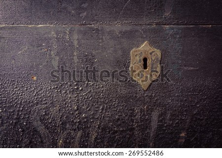 Front detail view of an old antique, vintage, black painted wooden chest with gold colored metal antique keyhole. - stock photo