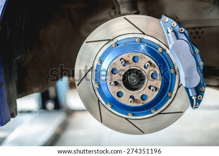 Front disc brake on car in process of new tire replacement - stock photo