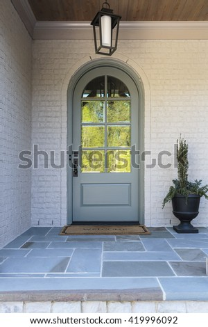 Front door, front view of an arched door with reflection