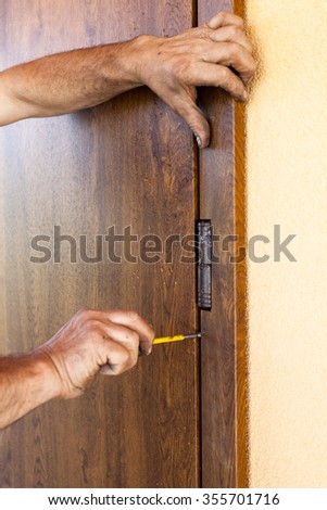 Front door installation. Worker fastens door trims with screwdriver