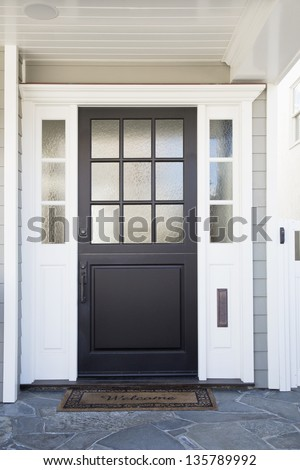 Front door of an upscale home/Vertical shot of a black front door of an upscale home with reflection in the frosted windows and a welcome mat - stock photo