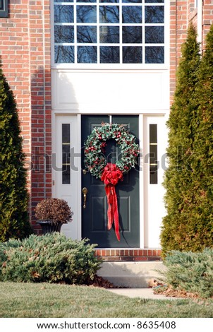Front door of single family home decorated with wreath and red bow
