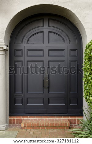 front door with large black arched doorway entrance. front view of large black doors - stock photo