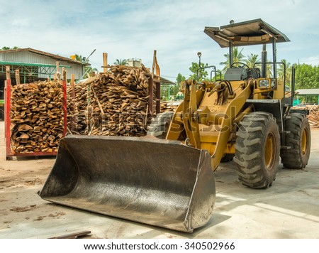 Front end loader and wood pile  - stock photo