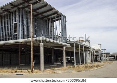 Front Facade of a Commercial real estate that is deserted, depressing and abandoned. Construction of property was not completed. - stock photo