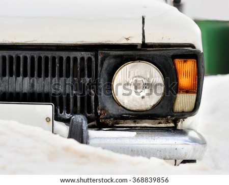 Front headlight of an old white car in winter. Snowfall - stock photo
