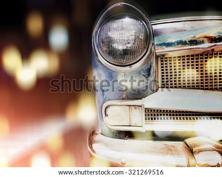 Front headlight of  old car with bokeh light blured and solf  vintage retro image. - stock photo