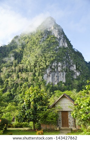 Front home in the morning, surrounded by forests and mountains - stock photo
