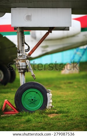 Front landing gear light aircraft on green grass. Shallow depth of field. Selective focus. - stock photo