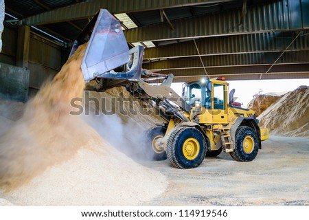Front loader emptying wood chips in pile for use in pellets manufacturing. - stock photo