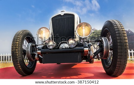 Front lower angle view of an unknown old-timer retro vintage sports car under blue sky - stock photo