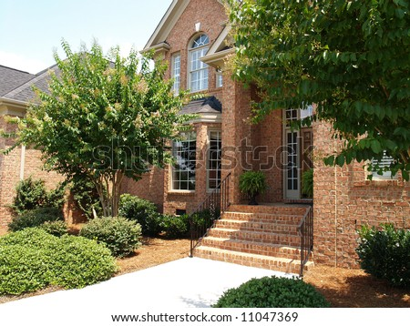 Front of a large brick home - stock photo