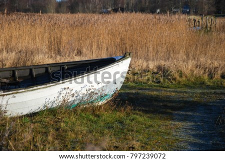 Front of an old white landed rowing boat