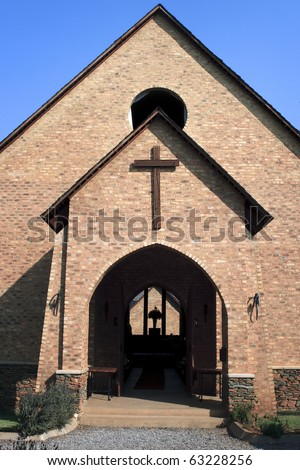Front of church with cross and open door - stock photo