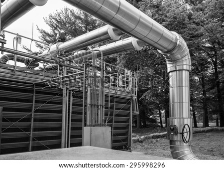 Front of cooling tower showing piping an valve.  Electrical conduits and mechanical system piping in a cooling tower yard. - stock photo