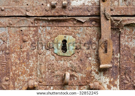 Front of old rusty chest with keyhole and bolt