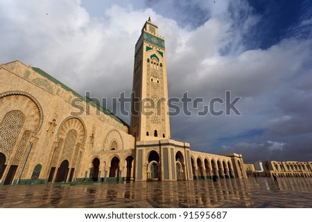 Front of ornate Hassan II Mosque showing rows of tiled archways and minaret.